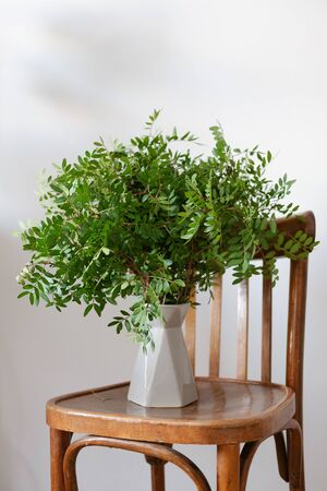 vase with a bouquet on a wooden chair. fragment of the interior in the Scandinavian style