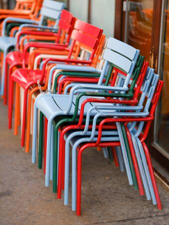 Many colorful chairs on the street next to the street cafe. Spare chairs for cafe visitors