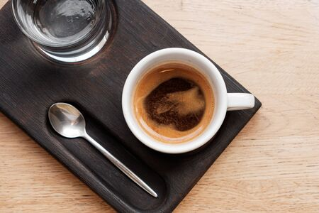 black coffee in a cup and a transparent glass with water on a wooden background. glare in the sun. Espresso Stockfoto