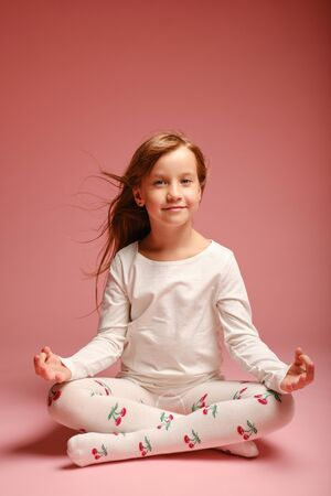 Bambina sveglia che si siede sul pavimento su uno sfondo rosa in studio. Scuola materna, infanzia, divertimento, concetto di famiglia. bambino alla moda