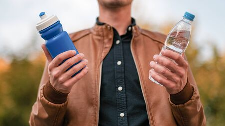 Hard choice. Concept of zero waste lifestyle of using refillable bollte instead of single use plastic