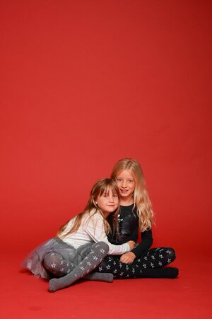 Two cute little girls are sitting next to each other on a red background in the studio. Kindergarten, childhood, fun, family concept. Two fashionable sisters posing.