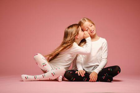 Due bambine carine si consultano in privato su uno sfondo rosa in studio. Scuola materna, infanzia, divertimento, concetto di famiglia. Una posa alla moda di due sorelle. Pettegolezzo Archivio Fotografico