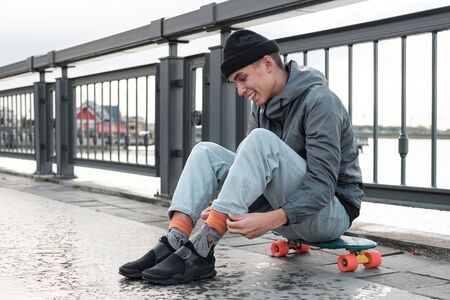 cheerful teenager sits on a penny board. Friendship, sport, youth.portrait. Sport lifestyle concept 版權商用圖片