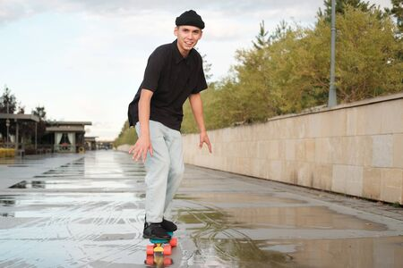 A young teenager rides on a penny board. a teenager in a black T-shirt, jeans and a black hat rides on a longord. Sport, active youth 版權商用圖片