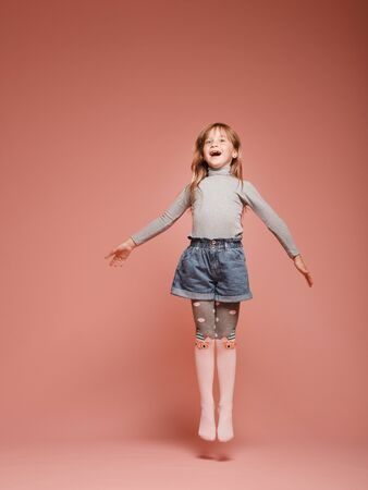 little pretty girl jumping on a pink background in the studio. Kindergarten, childhood, fun, family concept. Childrens fashion