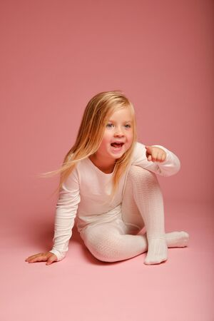 Cute little girl sitting on the floor on a pink background in the studio. Kindergarten, childhood, fun, family concept. fashion baby