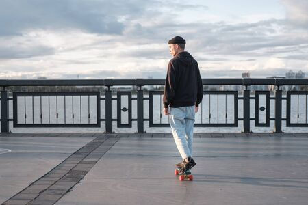 A young teenager rides on a longboard, starting at the foot. teenager in a hat and a black hoodie rides on a skateboard