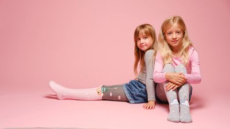 Two cute little girls are sitting next to each other on a pink background in the studio. Kindergarten, childhood, fun, family concept. Two fashionable sisters posing.