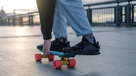 Young penny board in dark sneakers and jeans standing on a longboard. Fragment of a skateboard and legs close-up.