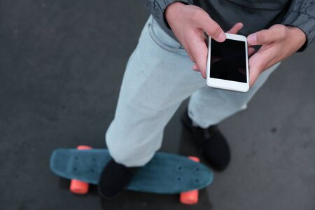 A young teenager is standing on a penny board with a phone in his hands. close-up