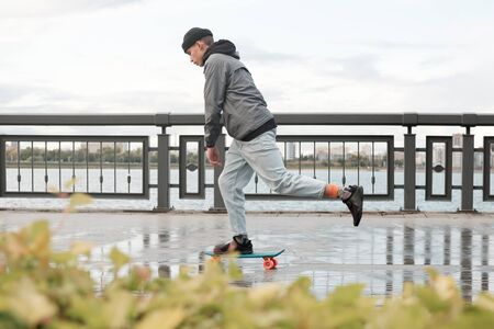 young teenager rides on a penny board, longboard, scooter board starting from the foot. teenager in a hat and youth clothes skates on a skateboard