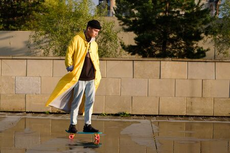 A young teenager rides on a penny board. a teenager in a yellow raincoat, jeans and a black hat rides on a longord. Sport, active youth