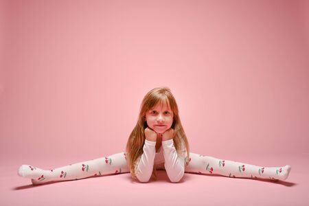 Little cute girl posing on a pink background in the studio. Kindergarten, childhood, fun, family concept. Childrens fashion Stockfoto