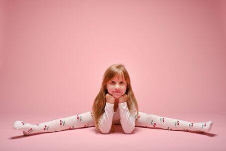 Little cute girl posing on a pink background in the studio. Kindergarten, childhood, fun, family concept. Childrens fashion 版權商用圖片
