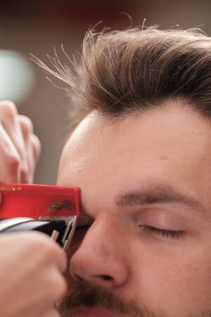 man with a beard cut eyebrows. close-up. Make eyebrows the right shape. barber haircut