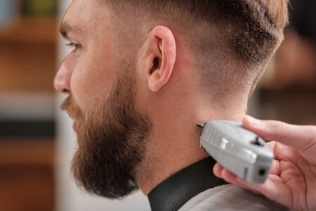 a man cuts his hair at a hairdresser in a barbershop. side view, close-up. Hipster.shave your head