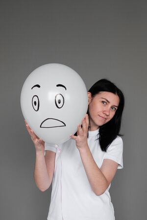 A girl in a white T-shirt with black hair holds in her hand a white balloon with a surprised emotion. Human emotions. Girl holds a balloon in her hand