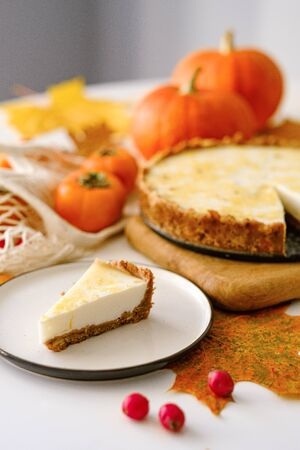 pumpkin cheesecake with persimmon. Autumn composition with leaves, persimmons and pumpkin. Thanksgiving concept. Halloween