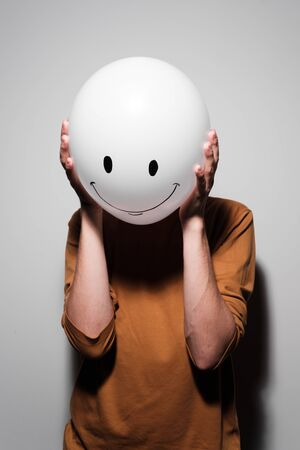 A man holding white balloon with smile face emotion instead of head. Positive Thinking concepts. hiding some bad feeling just keep smiling