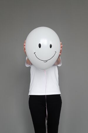 A woman holding white balloon with smile face emotion instead of head. Positive Thinking concepts. hiding some bad feeling just keep smiling