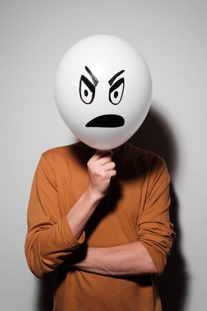 A man holding white balloon with an evil emotion instead of head. Negative Thinking concepts. A man holds a balloon in her hand Stockfoto