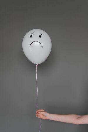 Balloon with sad emotion in a human hand on a gray background. Emotion concept