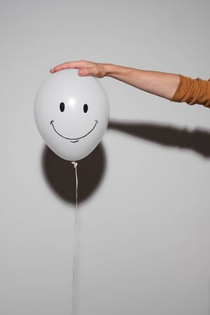 Balloon with a smile emotion in a human hand on a gray background. Emotion concept