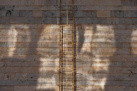 old rusty fire escape against a gray wall of concrete blocks 스톡 콘텐츠