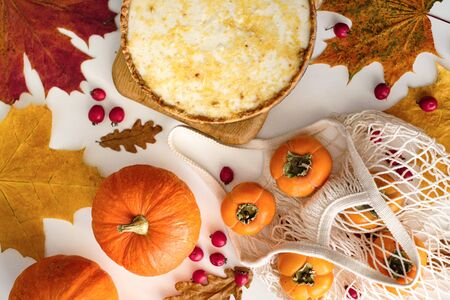 pumpkin cheesecake with persimmon, top view. Autumn composition with leaves and berries. Thanksgiving concept. Halloween