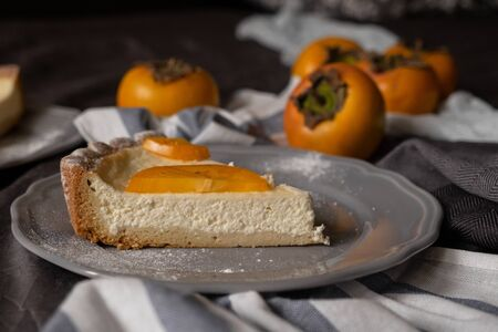persimmon cheesecake on a dark background. Pieces of cake decorated with persimmons and Christmas tree branches. top view