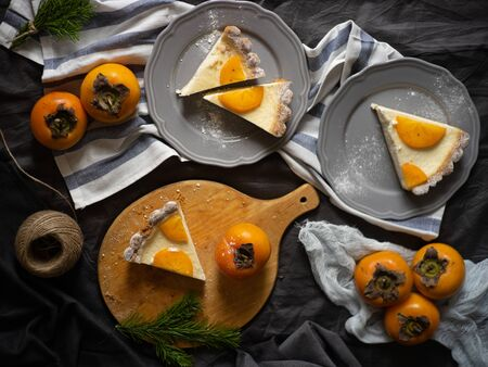 slices of persimmon cheesecake on beautiful plates. dark background. Cake for the holiday