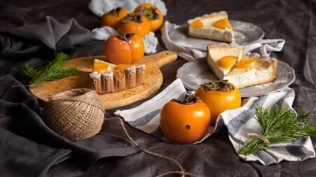 cheesecake and persimmons, dark gray background. rustic breakfast concept. top view