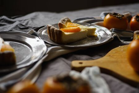 original persimmon cheesecake.side view. Beautiful dessert on a gray background. New Year. Christmas. Halloween Thanksgiving Day.