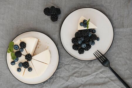 cheesecake New York with fresh berries and a slice on a plate decorated with blueberries and blackberries. Grey background. Minimalism. Delicious breakfast conception
