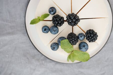 delicious creamy cheesecake with blueberries and blackberries. view from above. grey background. minimalism