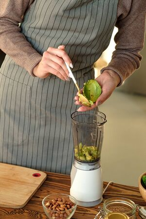 green smoothie preparation process. girl adds avocado to the blender. veggie concept. healthy food Stock Photo