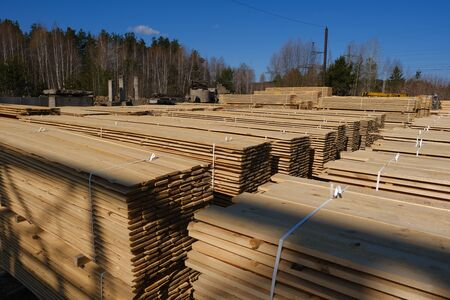 Piles of wooden boards in the sawmill. Warehouse for sawing boards on a sawmill outdoors. Timber mill, sawmill: storage of planed wooden boards