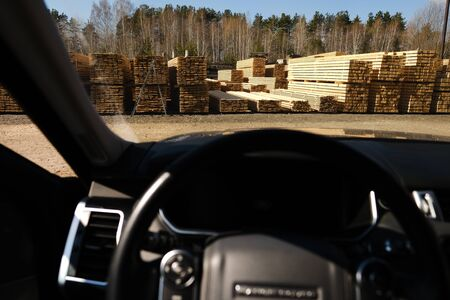 Sawmill from a car window. Warehouse for sawing boards on a sawmill outdoors. Timber mill: storage of planed wooden boards. Stok Fotoğraf