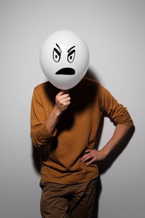 A man holding white balloon with an evil emotion instead of head. Negative Thinking concepts. A man holds a balloon in her hand 免版税图像