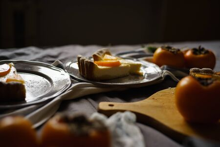 Beautiful persimmon cheesecake on a dark background. Thanksgiving concept.