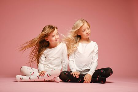 Two cute little girls are sitting next to each other on a pink background in the studio. Hair fluttering in the wind. Kindergarten, childhood, fun, family concept. Two fashionable sisters posing.