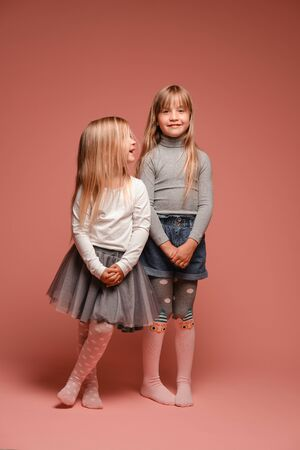 Two cute little girls are standing next to each other on a pink background in the studio. Kindergarten, childhood, fun, family concept. Two fashionable sisters posing. Stock fotó