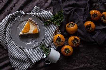Christmas persimmon cake. Cheesecake. New year dessert. dark background