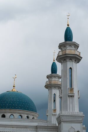 Towers of a mosque with a blue roof. Islam is a religion. Muslim mosque on sky background Stock Photo