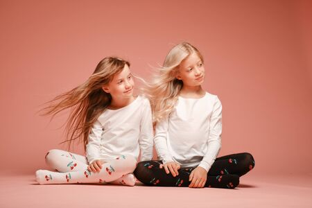 Two cute little girls are sitting next to each other on a pink background in the studio. Hair fluttering in the wind. Kindergarten, childhood, fun, family concept. Two fashionable sisters posing. Stock Photo