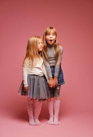 Due bambine carine sono in piedi l'una accanto all'altra su uno sfondo rosa in studio. Scuola materna, infanzia, divertimento, concetto di famiglia. Una posa alla moda di due sorelle.