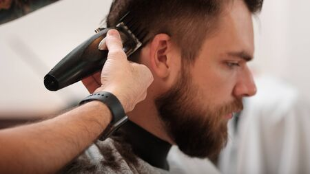 a man cuts his hair at a hairdresser in a barbershop. side view, close-up. Hipster.shave your head Stock Photo