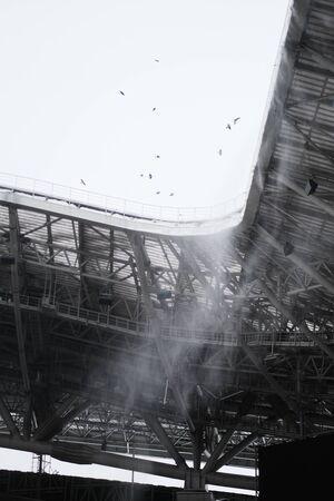 birds take off over a sports stadium. Sports Stadium