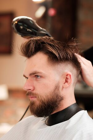 Fashionable man with a beard makes a hairstyle. hairdresser sprays hairspray on her hair. finishing touch finishing image.